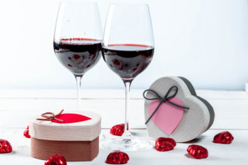Glasses of red wine with gifts and chocolates