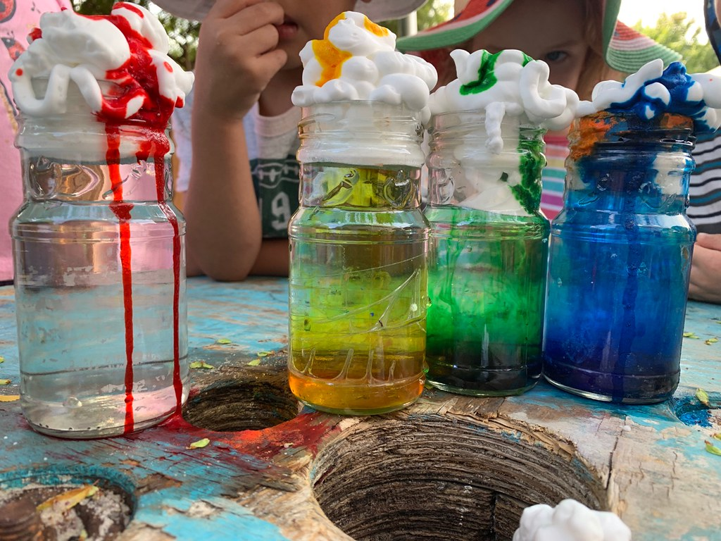 Glass jars filled with water, topped with shaving cream clouds, and food colouring rain