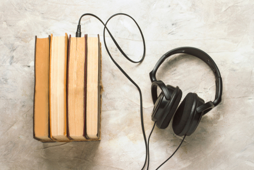 Books,And,Headphones,Connected,To,Them,On,A,White,Stone