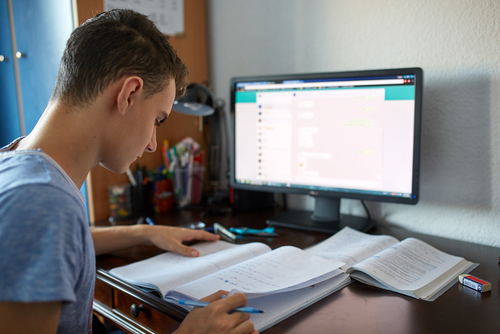 Teenager,Boy,Doing,Homework,On,His,Desk,At,Home