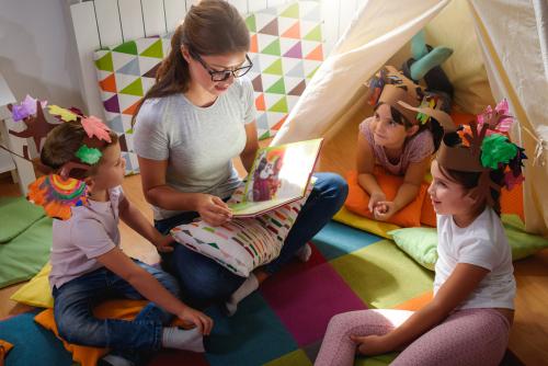 Preschool,Teacher,Reading,A,Story,To,Children,At,Kindergarten.,Mother