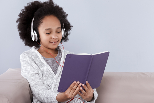 Pretty,Little,Girl,In,Headphones,Holding,Notebook,And,Smiling,While